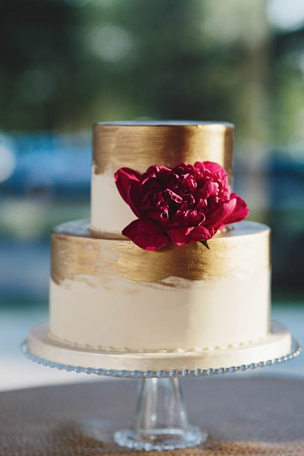 chic gold brushed wedding cake with marsala red flower