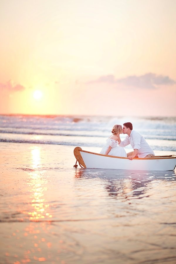 romantic kiss of bride and groom in the boat