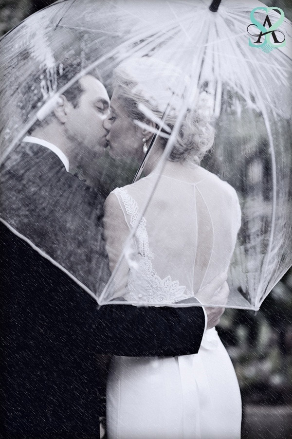 romantic kiss wedding photos of bride and groom under umbrella