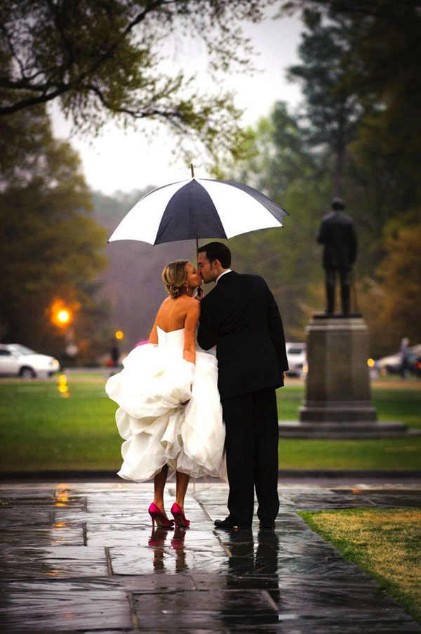 sweet kiss of bride and groom in the city street