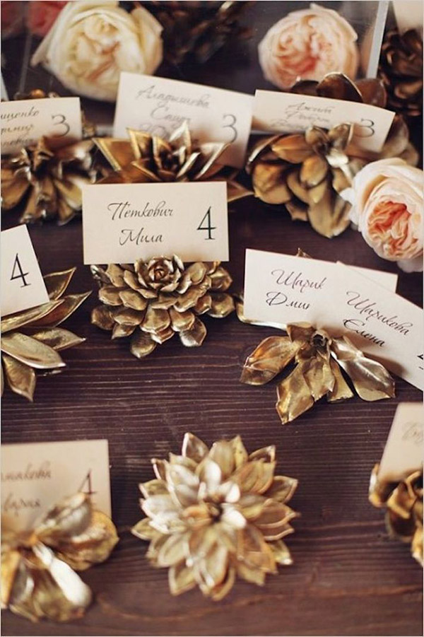 gold painted pinecone escort card-winter wedding ideas