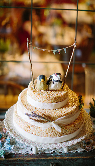 two-tiered rice krispy wedding cake topped with bird cake toppers