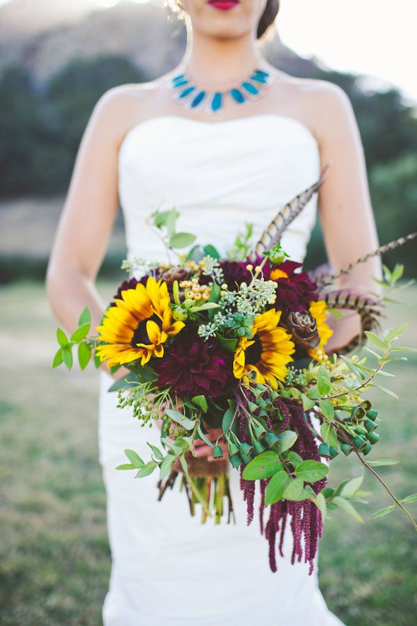 Jewel tone wedding bouquet with sunflowers dahlias greenery and feathers