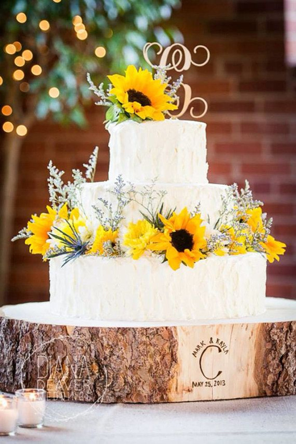 elegant simple wedding cake with sunflower and wooden stand