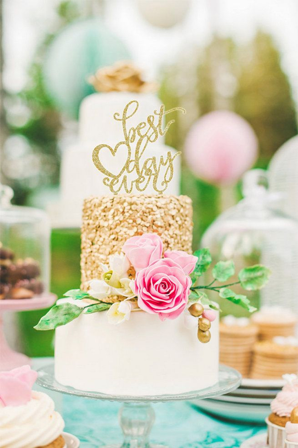 gold glittery wedding cake with cute cake toppers