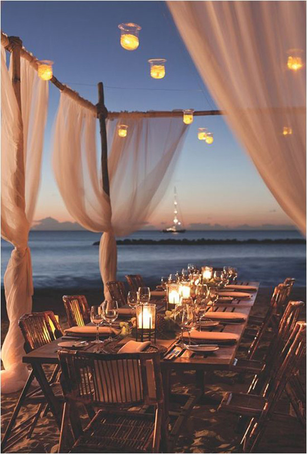 outside beach reception with floating candle lighting