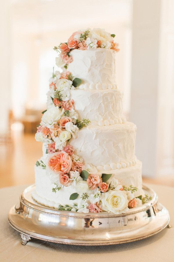 beautiful wedding cake with cascading peach flowers