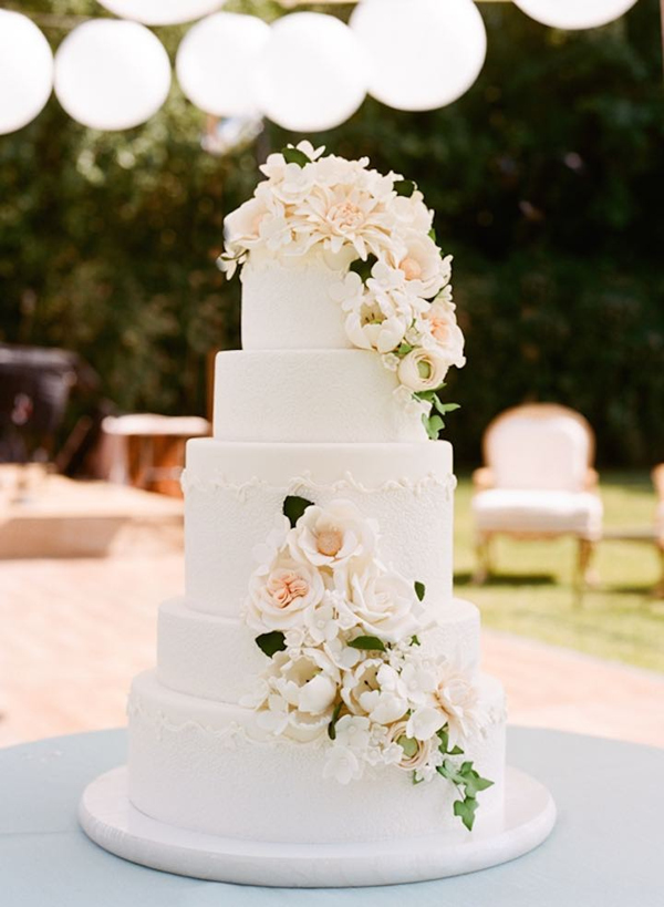 simple elegant five tiered wedding cake with cascading flower decorations