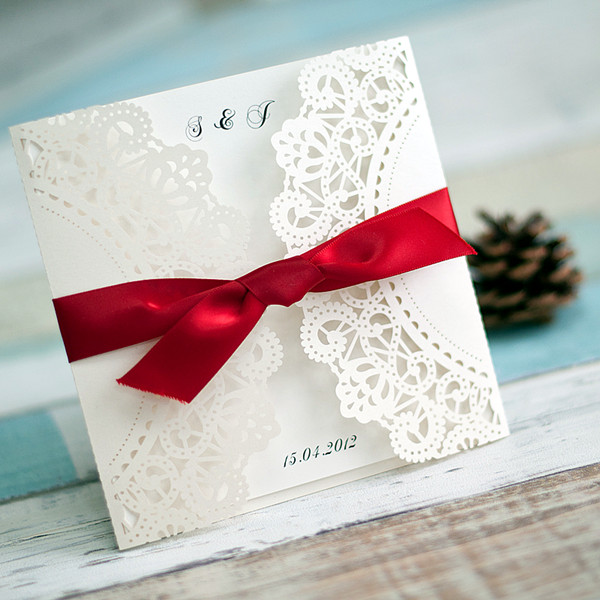 classic white laser cut wedding invitations with red ribbon