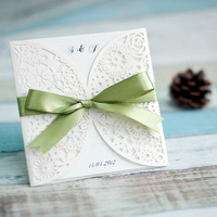 white laser cut wedding invitation with sage ribbons