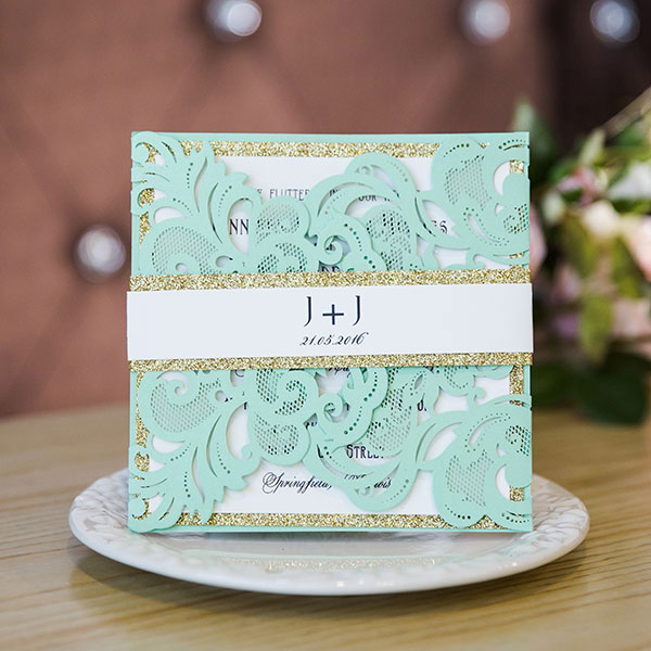 seafoam green laser cut wedding invitations with glittery bellybands