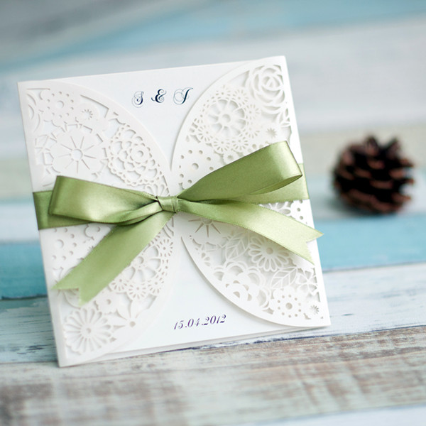 simple white laser cut wedding invitation with green bow