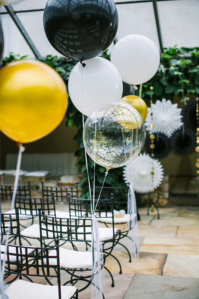 black, white and gold balloon wedding aisle chair decoration