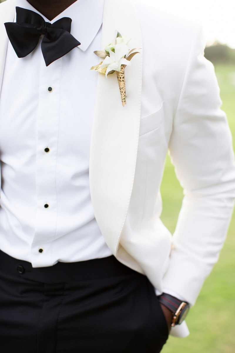 white suit jacket, boutonniere with gold detailing wedding attire