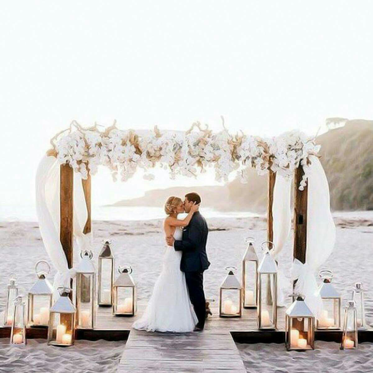 eautiful beach wedding Arch with flowers and lanterns