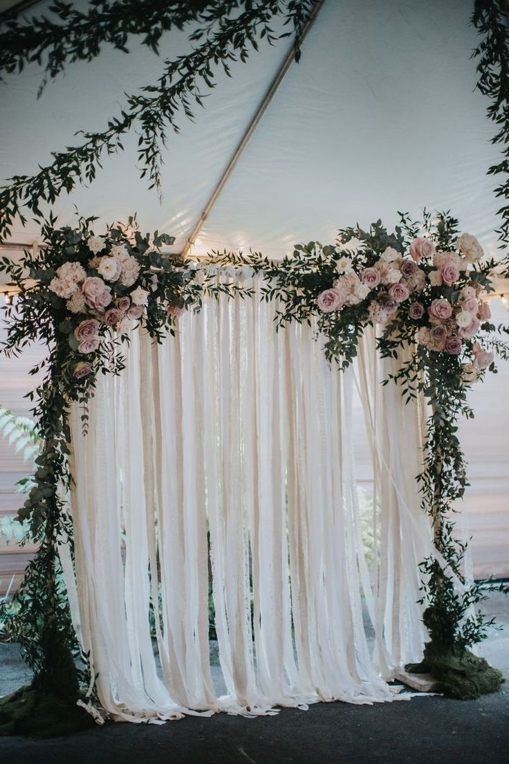 Floral wedding arch with blush pink flowers and ribbon backdrop