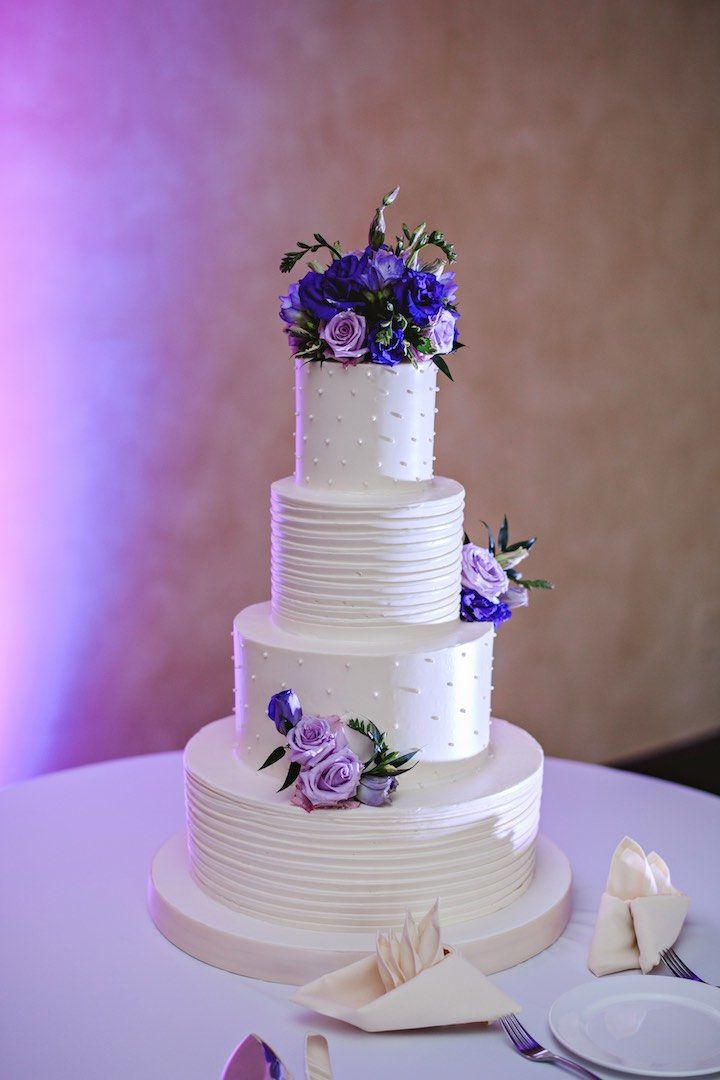 Romantic white wedding cake with purple flowers