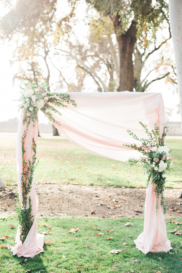 blush pink wedding ceremony altar with draped fabric and greenery