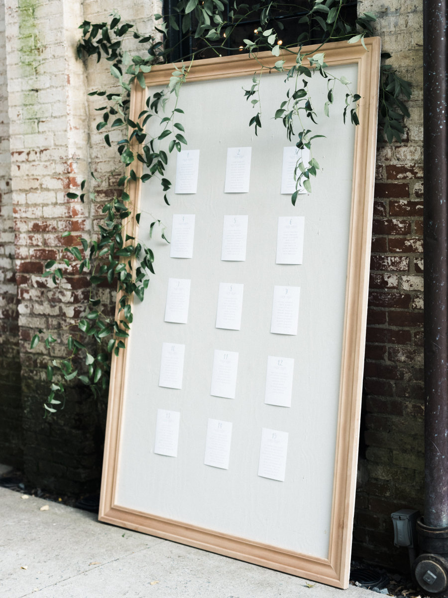 giant wedding seating chart board with greenery
