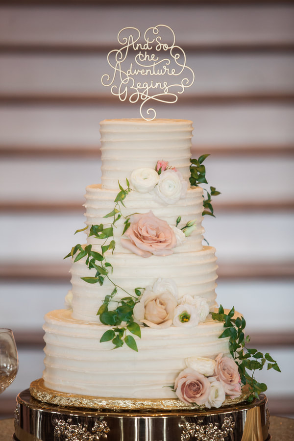 white wedding cake with blush rose and greenery