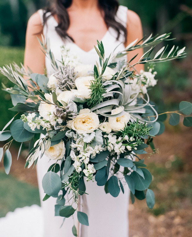 organic wedding bouquet with lots of greenery and cream peonies