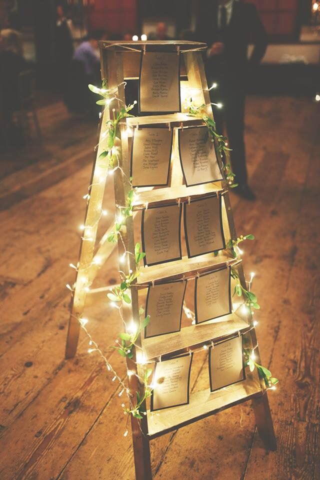 ladder wedding table plan ideas with ivy wrapped around xmas lights