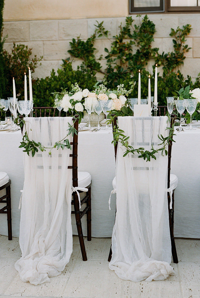 stunning white and greenery bride and groom wedding chairs