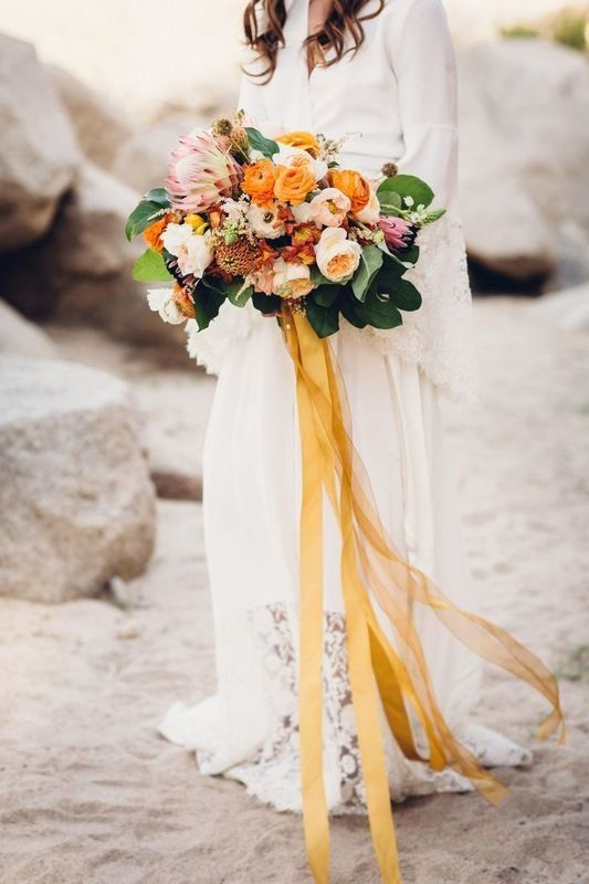 colorful peach and yellow bouquet with garden roses, ranunculus and king protea