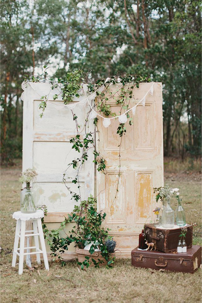 greenery old door wedding ceremony backdrop with suitcases