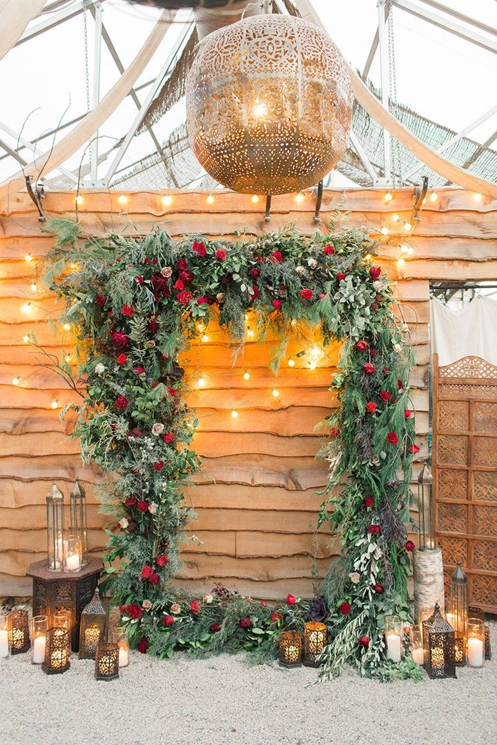 lush greenery and red floral christmas wedding arch ideas