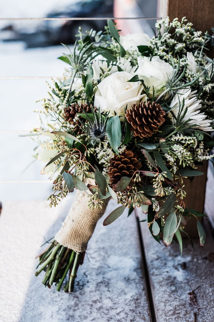 rustic winter wedding bouquet with white roses, eucalyptus and pine cones