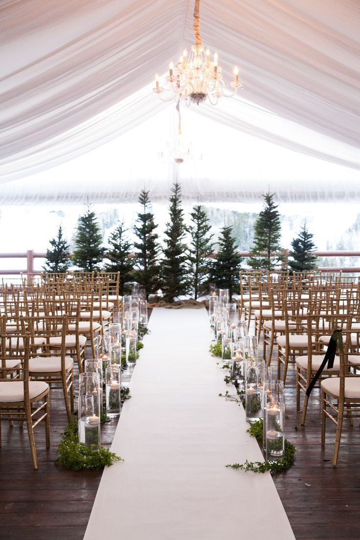fancy tented winter wedding ceremony with evergreen trees and candles