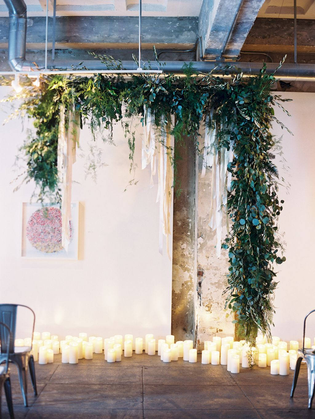 industrial chic hanging greenery garland wedding backdrop with candles