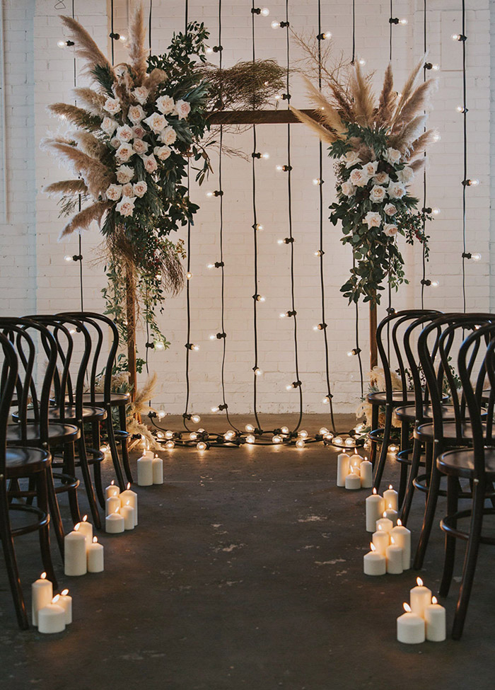 boho style floral wedding arch with pampas plumes and lights