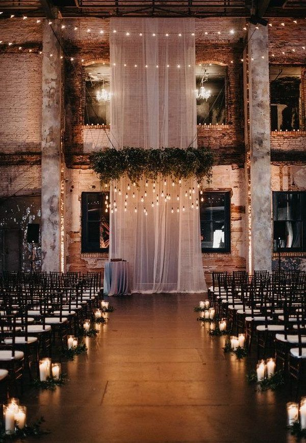dramatic industrial wedding ceremony with drapery and candles aong the aisle