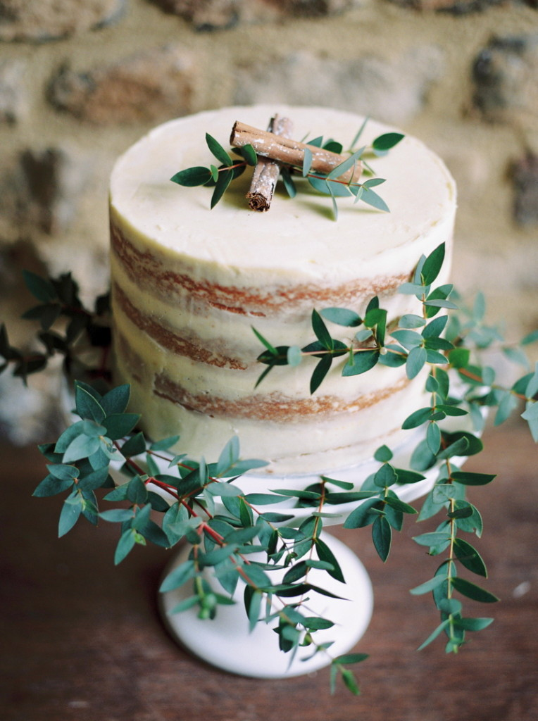 elegant small semi-naked wedding cake with green leaves