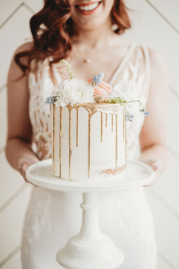 gorgeous gold drizzle wedding cake with dusty blue and blush flower