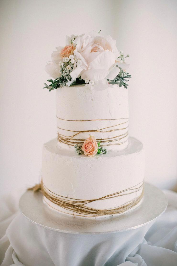 simple creative white twotier wedding cake with flowers with twine wraps