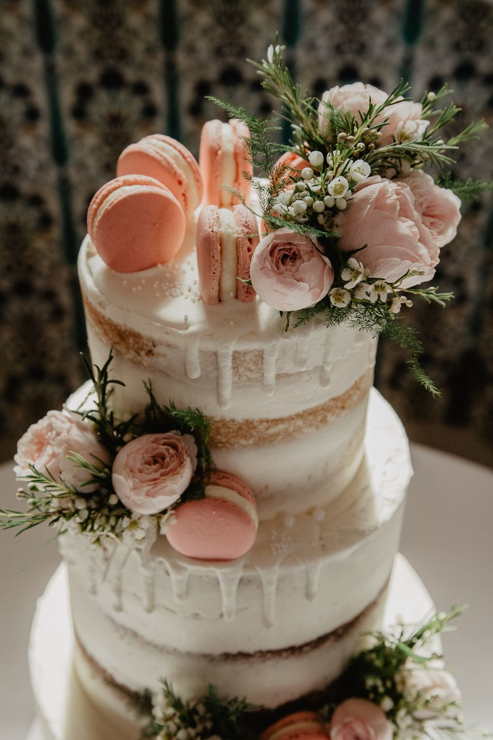 sweet pink drip and semi naked wedding cake with with macarons