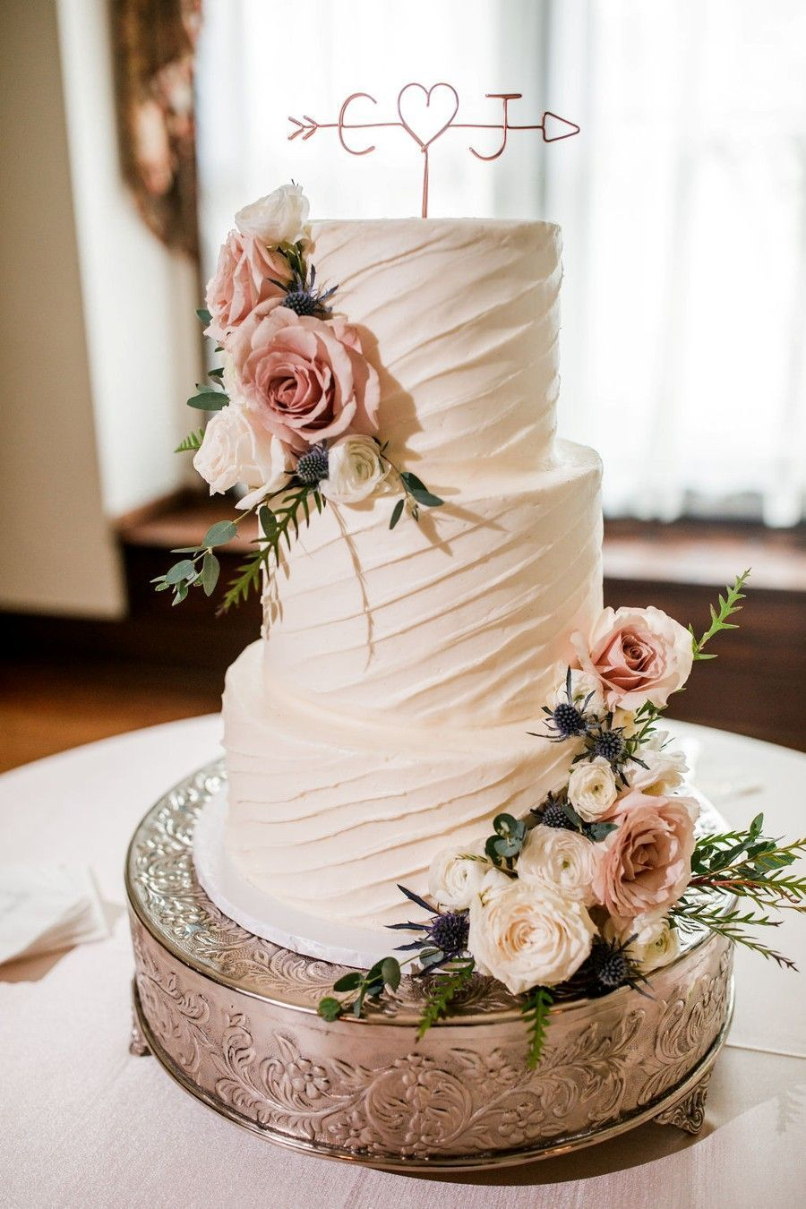 two tier flower wedding cake with arrow cake toppers