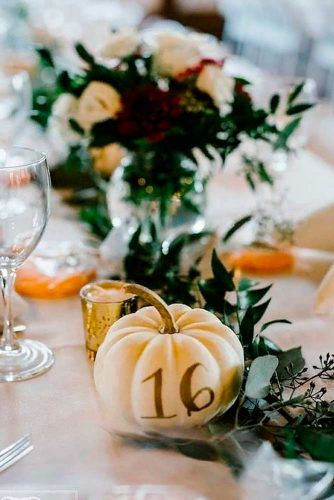 Unique wedding centerpieces of pumpkins with gold foiled wedding table numbers for fall wedding theme