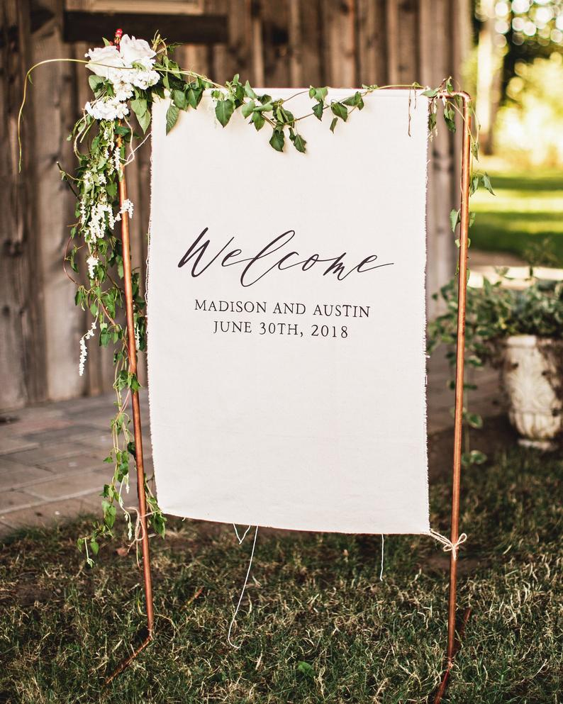 White fabric wedding signs with greenery and flowers perfet for outdoor wedding theme