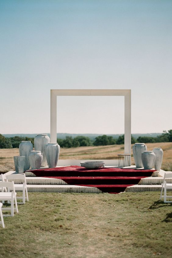 a natural backdrop with a minimalist white arch and vases around the arch