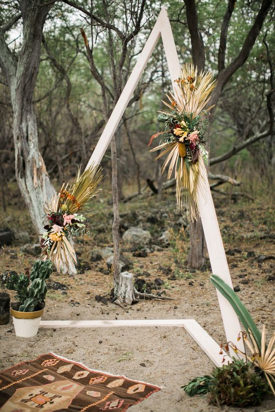 a triangle wedding arbor decorated with bold blooms, dried tropical leaves, herbs and succulents for a desert feel