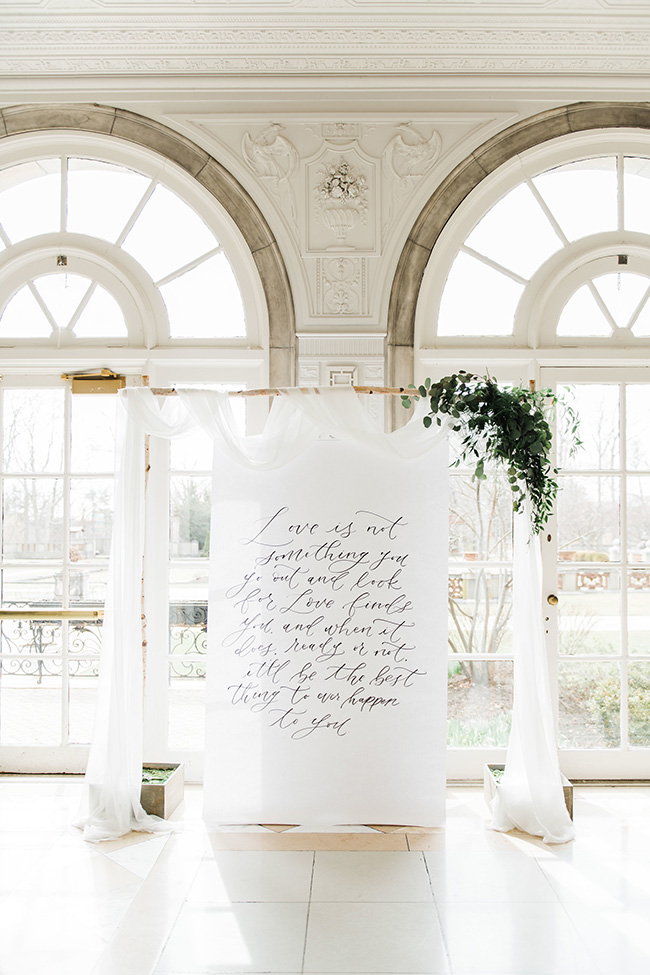 cool white greenery minimal indoor wedding arch with calligraphy wedding quotes