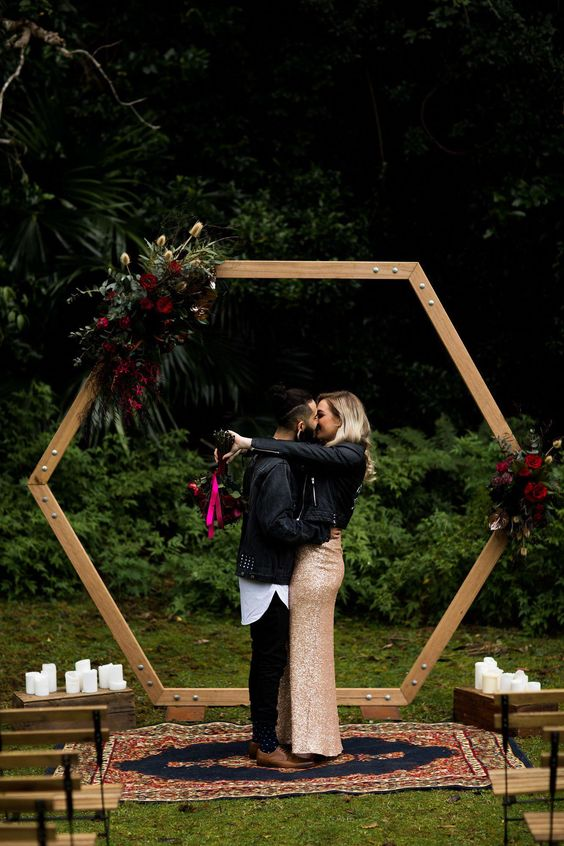 hexagon arbor arch with greenery and burgundy and purple blooms plus candles around for a fall boho wedding