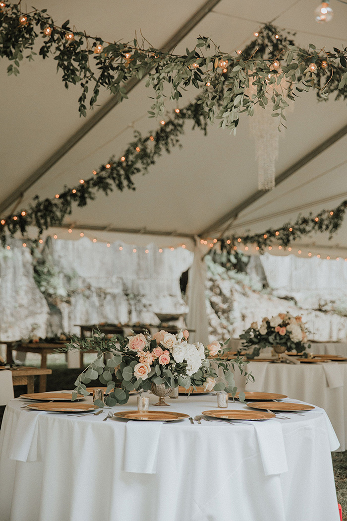 elegant tented wedding reception with bistro lights and greenery