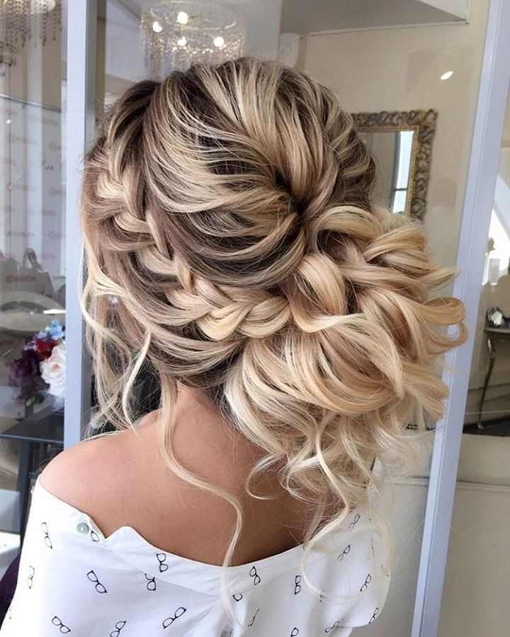 messy bun updo with curls and a braid