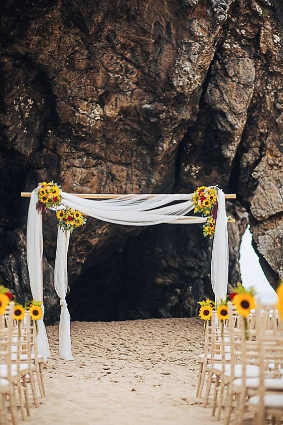 simple flowy fabric wedding arch with sunflowers
