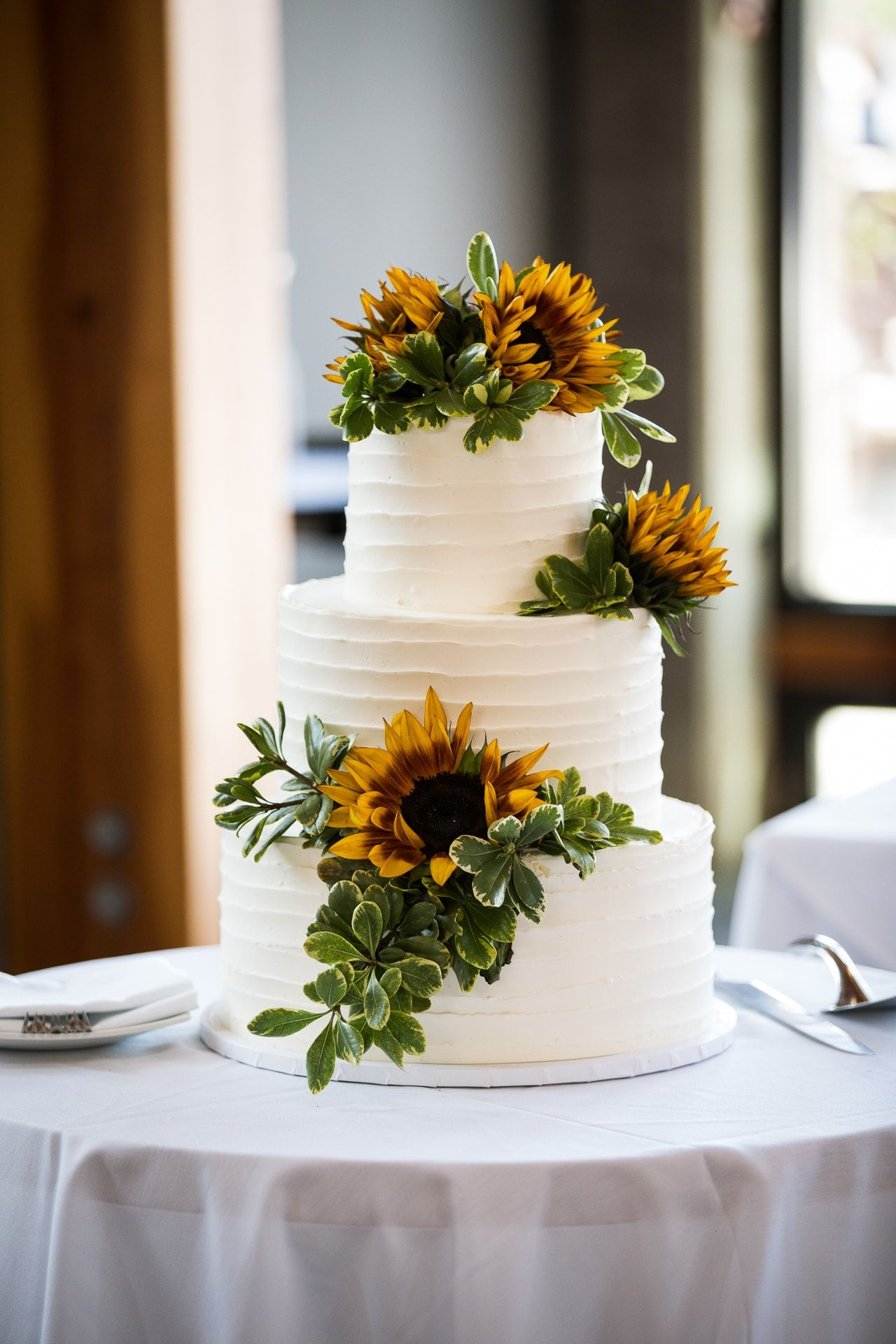 simple sunflower and green leaves wedding cakes